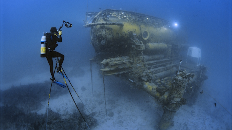 Brian sits atop a six-metre high underwater tripod to photograph the Aquarius Habitat off Key Largo, Florida; he lived inside this habitat in saturation for seven days. [© Mark Conlin]