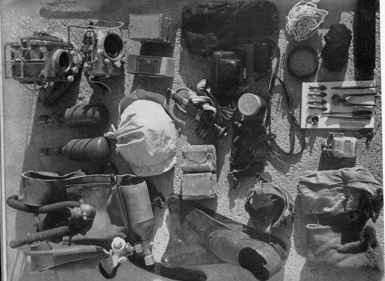 "1948. The equipment that Hans took with him on his solo expedition to the Red Sea. ""My equipment includes the respirator (upper right), oxygen cylinders, submarine cameras, fins, mask, light gauge, film-changing bag, and harpoon barbs. The bag in the centre contains enough caustic soda for only twenty-five descents of an hour each."" (Leslie Leaney Archives)"