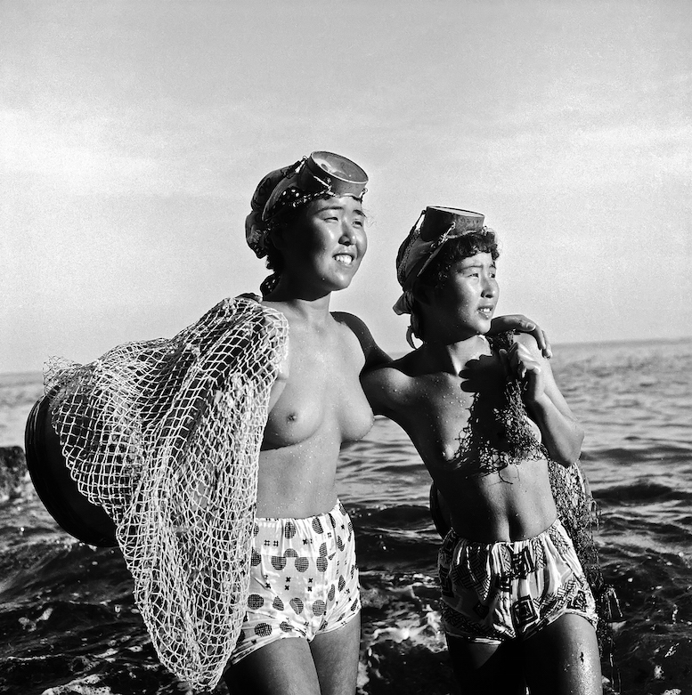 1947, Toba, Japan --- Two pearl divers wade in the surf carrying their nets. The young women harvest oysters implanted with pearls for the Mikomoto company in Toba Bay. --- Image by © Horace Bristol/CORBIS