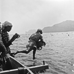 1947, Toba, Japan --- A pearl diver jumps into Toba Bay with her barrel and net from a boat. Young women harvest oysters implanted with pearls for the Mikomoto company. Image by © Horace Bristol/CORBIS