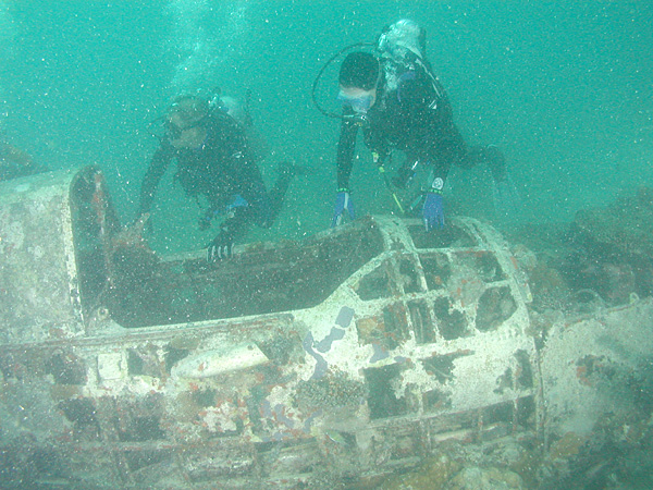 "Divers next to cockpit of Aichi E13 ""Jake"" floatplane wreck, Kavieng harbor, New Ireland. Papua New Guinea. © Aquaimages"