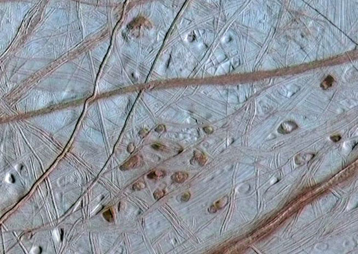 """The ruddy """"freckles"""" on Europa. The spots and pits visible in this region of Europa's northern hemisphere are each about 10 kilometres across. The dark spots are called """"lenticulae,"""" the Latin term for freckles. © NASA/JPL/University of Arizona/University of Colorado"""