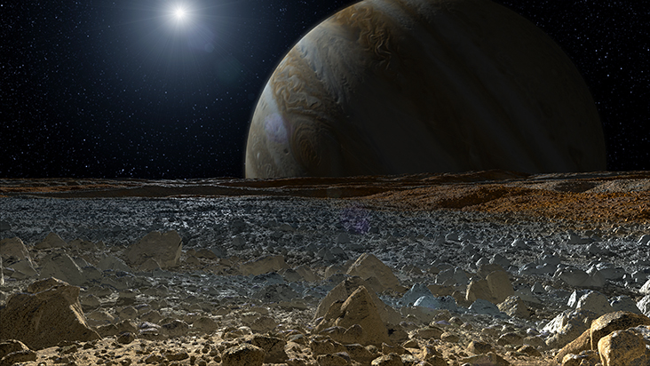 This artist's concept shows a simulated view from the surface of Jupiter's moon Europa. Europa's potentially rough, icy surface, tinged with reddish areas that scientists hope to learn more about, can be seen in the foreground. The giant planet Jupiter looms over the horizon. © NASA/JPL-Caltech