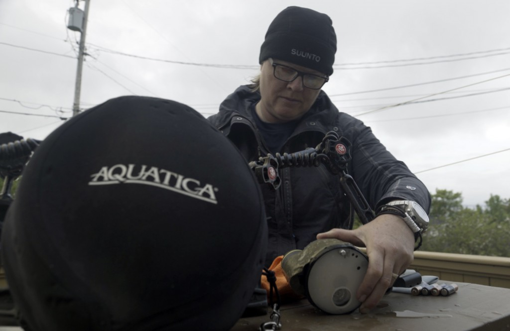 """""""There is a ton of gear to deal with on a technical dive. Add a camera system and lights and you are well burdened."""" Jill preparing camera gear"""