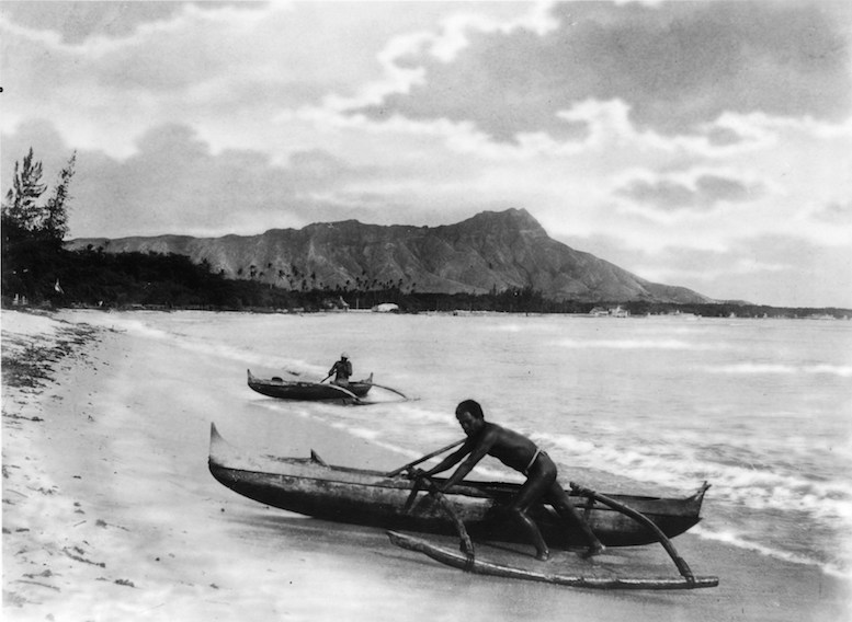 Two natives with outrigger canoes at the shoreline of Honolulu, Hawaii. © Wikimedia Commons